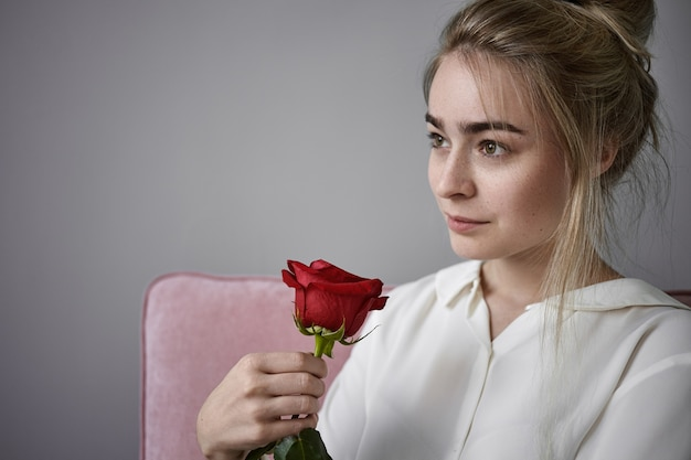 Concept de romance, d'amour et de beauté naturelle. bouchent la vue recadrée de la belle jeune femme romantique aux cheveux blonds portant un chemisier blanc assis isolé, sentant la rose rouge le jour de la saint-valentin