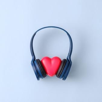 Concept romantique à la mode avec un casque de fête et un cœur à l'écoute de la discothèque. idée créative minimale.
