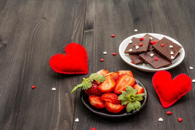 Concept romantique de la saint-valentin. chocolat, fraise mûre fraîche, coeurs en feutre rouge. dessert sucré pour les amoureux.