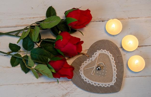 Concept romantique, trois roses rouges, coeur et bougies