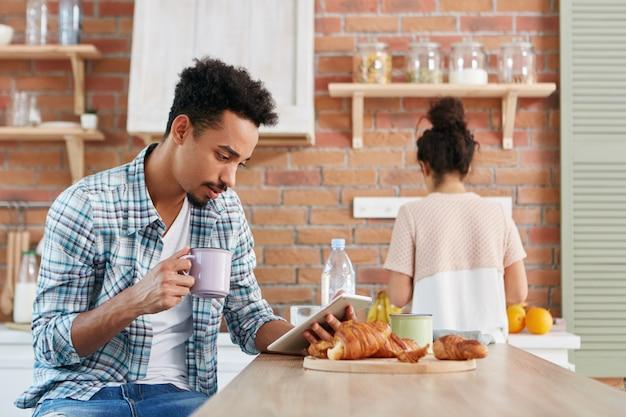 Concept de routine familiale. mâle de race mixte lit attentivement les nouvelles sur ordinateur tablette, s'assoit à la cuisine,