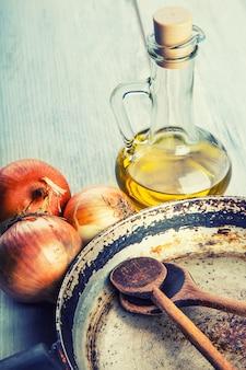 Concept rustique composé d'une vieille casserole avec des cuillères en bois posées sur une table en bois avec de l'oignon et de l'huile.