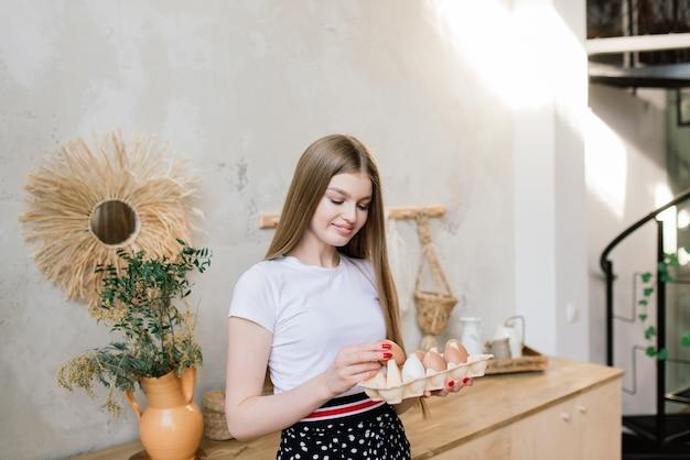Concept de saine alimentation. belle jeune femme avec des oeufs à la cuisine.