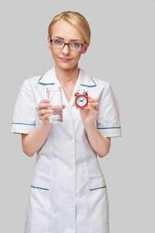 Concept de saine alimentation ou de mode de vie - femme médecin tenant et un verre d'eau douce claire et petit réveil rouge