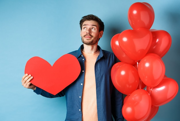 Concept de la saint-valentin et de l'amour. homme rêvant d'âme soeur, tenant une grande découpe de coeur rouge et des ballons, debout sur fond bleu.