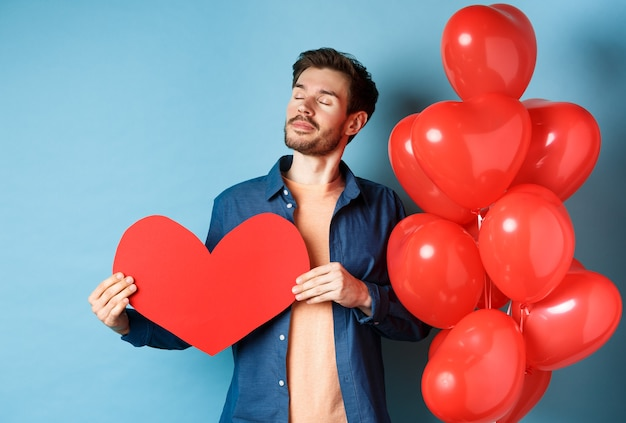 Concept de la saint-valentin et de l'amour. homme rêveur aux yeux fermés, tenant la découpe de coeur rouge romantique et debout près des ballons de coeurs, fond bleu.