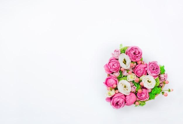 Concept de la saint-valentin. boîte en forme de coeur fleur sur fond blanc avec un espace vide pour le texte. vue de dessus, pose à plat.