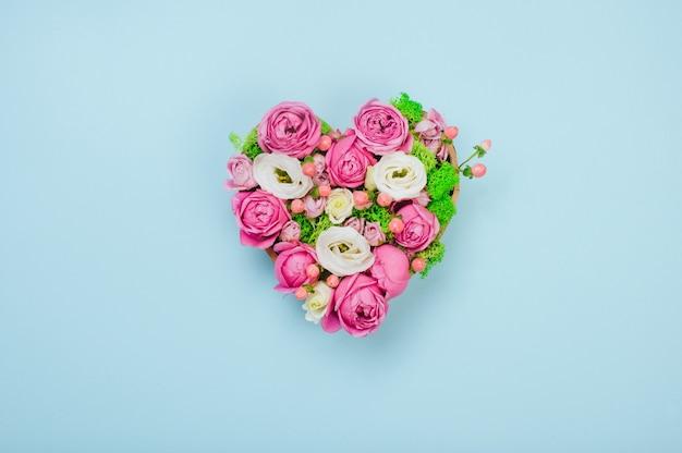 Concept de la saint-valentin. boîte en forme de coeur fleur sur fond bleu avec un espace vide pour le texte. vue de dessus, pose à plat.