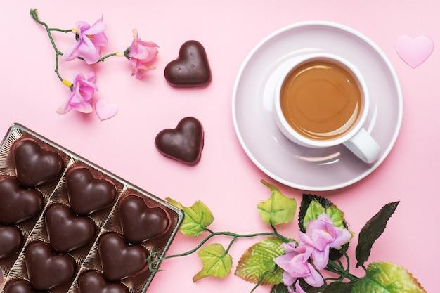 Concept de la saint-valentin. bonbons au chocolat et café, coeurs sur fond rose. espace de copie plat. carte de voeux et cadeau.