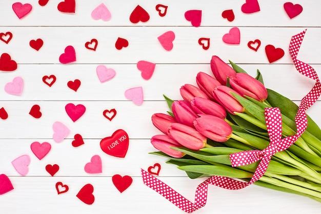 Concept de saint valentin. bouquet de tulipes roses à décor de coeurs.