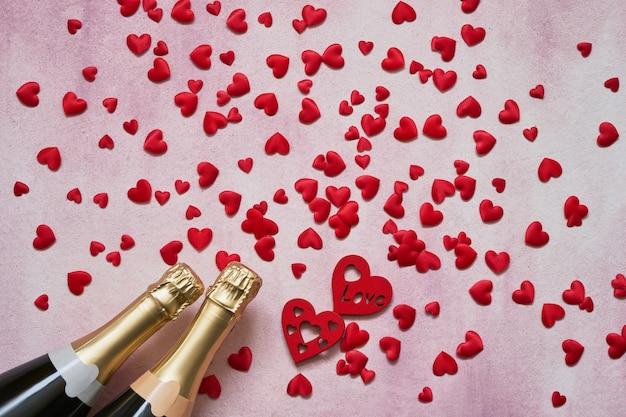 Concept de saint valentin. bouteilles de champagne avec des coeurs rouges sur fond rose.