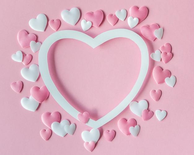 Concept de la saint-valentin. carte de voeux avec un cœur rose et blanc et un espace pour le texte. vue de dessus. mise à plat.