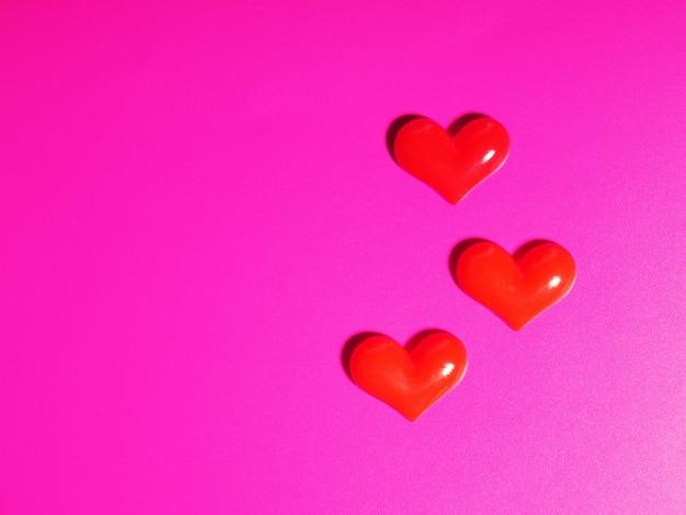 Concept de la saint-valentin, coeur argent et rouge sur fond rose, carte de voeux.