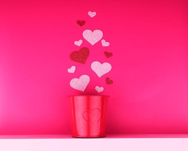 Concept de la saint-valentin, coeur argent et rouge et pot en fer rouge se dresse sur une étagère blanche.