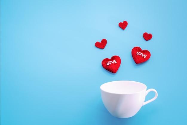 Concept de la saint-valentin. coeur rouge avec une tasse de café blanche sur fond bleu