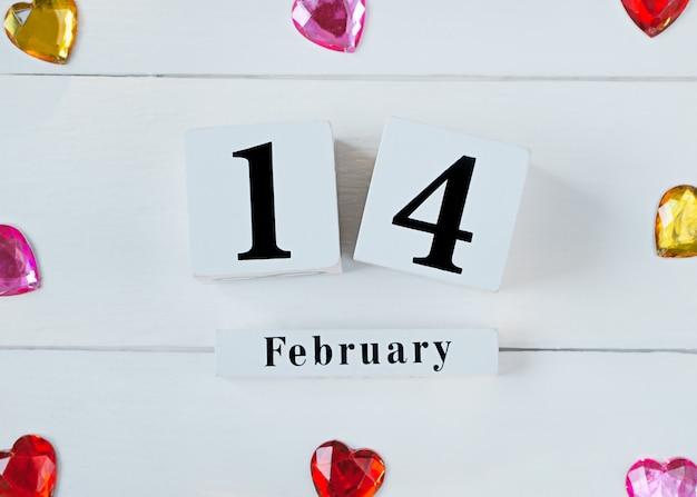 Concept de la saint-valentin avec coeurs et calendrier de bloc en bois le 14 février.