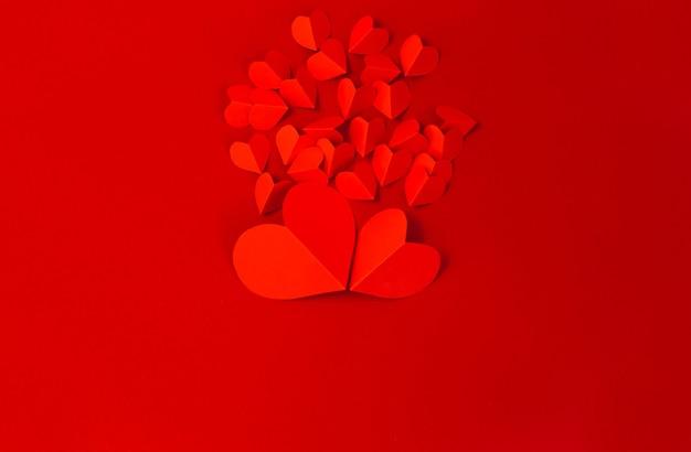 Concept de la saint-valentin avec des coeurs rouges sur fond rouge, mise à plat, espace de copie