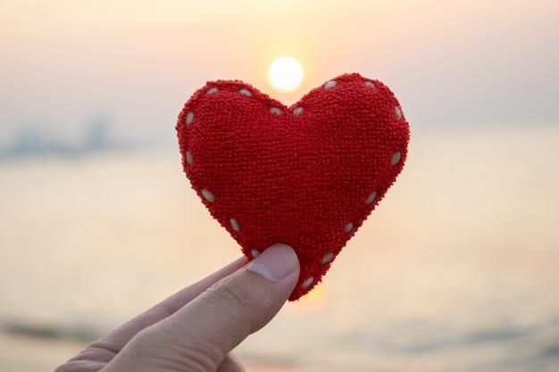 Concept de saint valentin, concept de l'amour, main de femme tenant un coeur rouge sur fond de coucher de soleil.