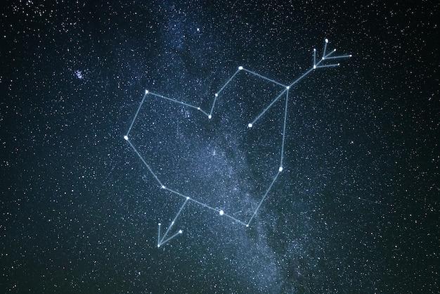 Concept de la saint-valentin. une constellation d'amour dans le ciel étoilé. coeur et flèche de cupidon