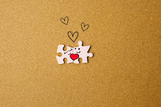 Concept de la saint-valentin. couple de puzzles avec des coeurs sur un fond d'or.