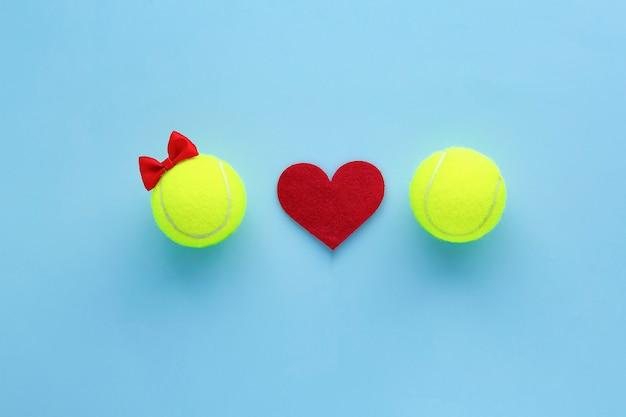 Concept de la saint-valentin. deux balles de tennis jaunes et coeur rouge.