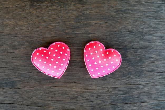 Concept de la saint-valentin, deux coeurs roses sur fond en bois.
