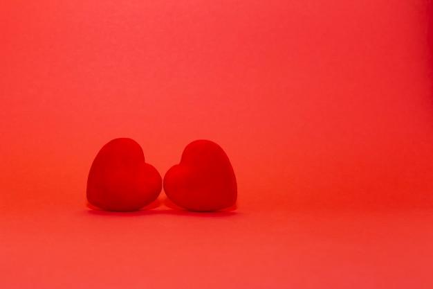 Concept de la saint-valentin, deux coeurs rouges en velours sur fond rouge. espace libre pour le texte.