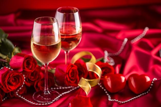 Concept de la saint-valentin ou du mariage. coupes à vin roses rouges et cadre romantique pour deux en rouge. carte de voeux pour jubilé ou anniversaire.