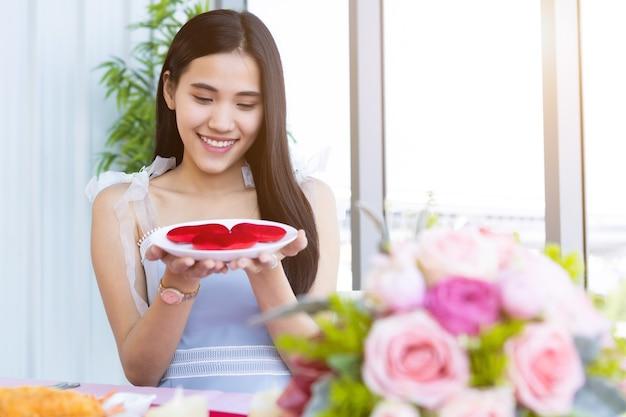 Concept de la saint-valentin, heureuse de sourire jeune femme asiatique assise à une table food show tenant un petit coeur rouge en forme de plaque à l'arrière-plan du restaurant