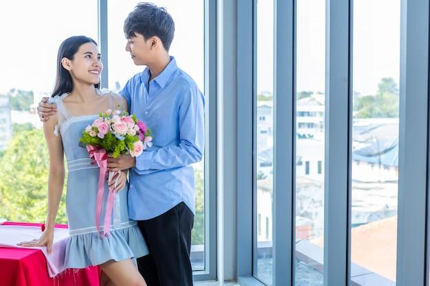Concept de la saint-valentin, jeune couple asiatique heureux tenant un bouquet de roses rouges et roses après le déjeuner dans un fond de restaurant, couple d'histoire d'amour