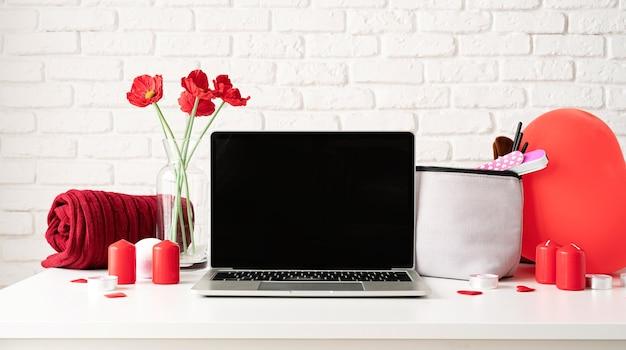 Concept de saint valentin et de la journée des femmes. ordinateur portable avec accessoires cosmétiques et spa