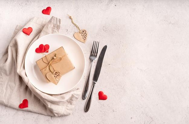 Concept de saint valentin et de la journée des femmes. réglage de la table de la saint-valentin avec un coffret cadeau écologique