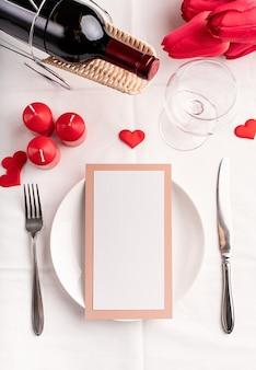 Concept de saint valentin et de la journée des femmes. réglage de la table de la saint-valentin avec menu, assiette, bouteille de vin vue de dessus, maquette de conception