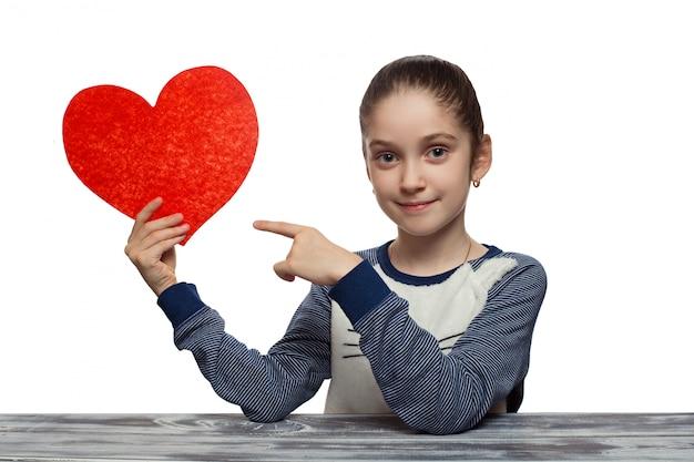 Concept de la saint-valentin - petite fille avec coeur rouge. isolé sur fond blanc modèle féminin de studio