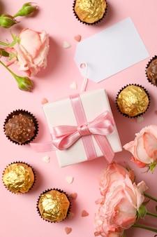 Concept de la saint-valentin avec des roses, des bonbons et une boîte-cadeau sur fond rose