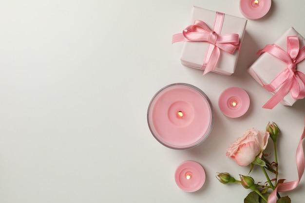 Concept de la saint-valentin avec des roses, des coffrets cadeaux et des bougies sur fond blanc