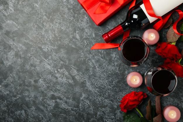 Concept de la saint-valentin avec des roses et du vin sur une table fumée noire