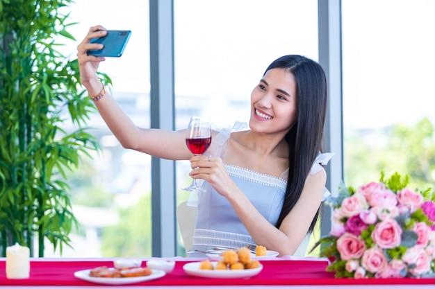 Concept de la saint-valentin, selfie of happy of smiling asian young woman sitting at a table food holding with wine verres à l'arrière-plan du restaurant