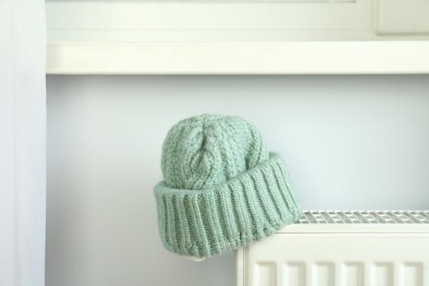 Concept de saison de chauffage avec bonnet tricoté sur radiateur.