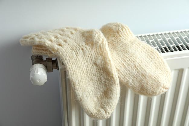 Concept de saison de chauffage avec chaussettes tricotées sur radiateur.
