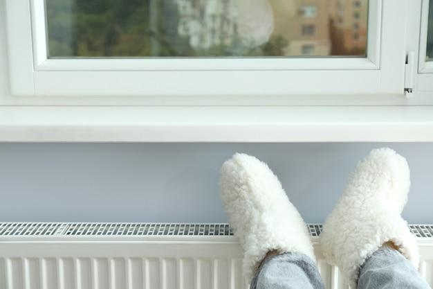 Concept de saison de chauffage avec jambes en bottes tricotées sur radiateur.