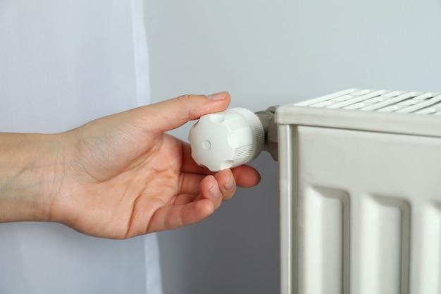 Concept de saison de chauffage avec la main ajuste le radiateur.