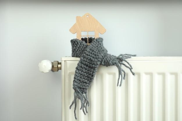 Concept de saison de chauffage avec maison en bois sur radiateur de chauffage.