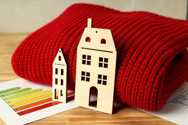 Concept de saison de chauffage avec pull rouge sur table en bois.
