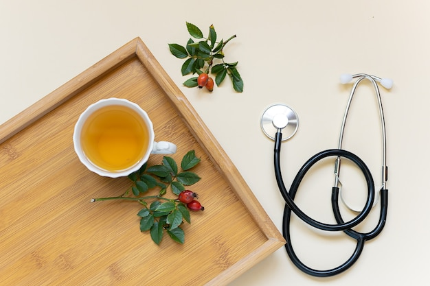 Concept de saison de la grippe. tasse de tisane vitaminée sur le plateau en bois et stéthoscope médical.