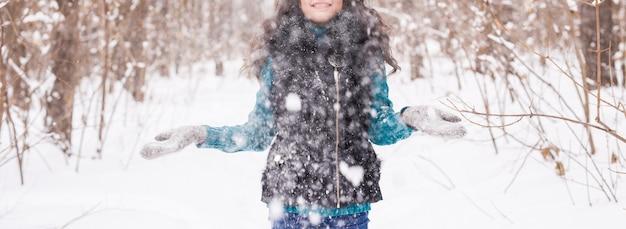 Concept de saison, de loisirs et de personnes - le gros plan d'une femme est heureuse et jette de la neige dans la nature hivernale
