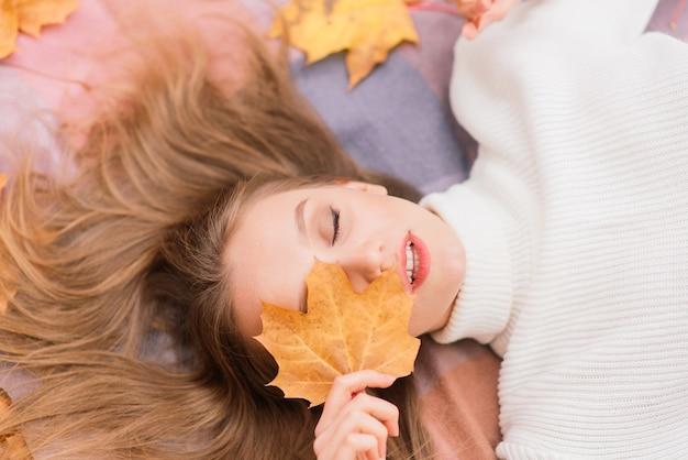 Concept de saison et de personnes - belle jeune femme avec des feuilles d'érable d'automne allongées sur le sol