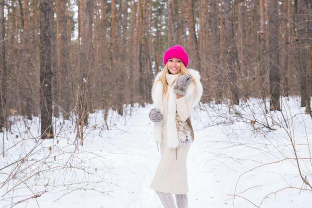 Concept de saison et de personnes - jolie femme blonde habillée en blouse blanche et chapeau rose debout dans le parc enneigé d'hiver