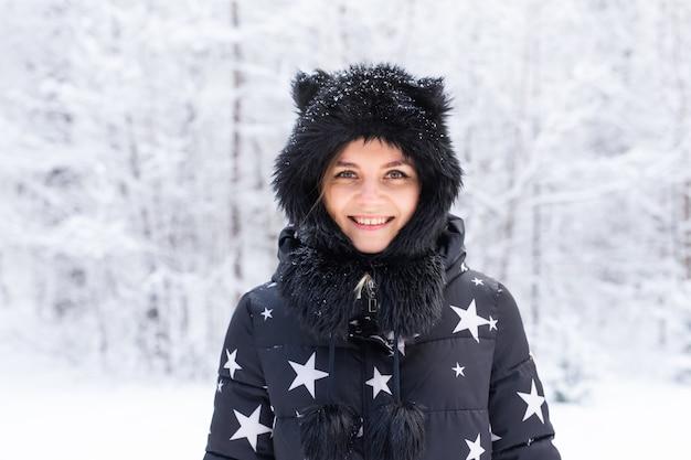 Concept de saison et de personnes - portrait en plein air d'hiver de belle jeune femme.