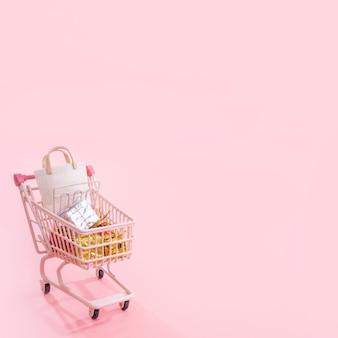 Concept de saison shopping vente annuelle - mini chariot de magasin rouge plein de sac en papier cadeau isolé
